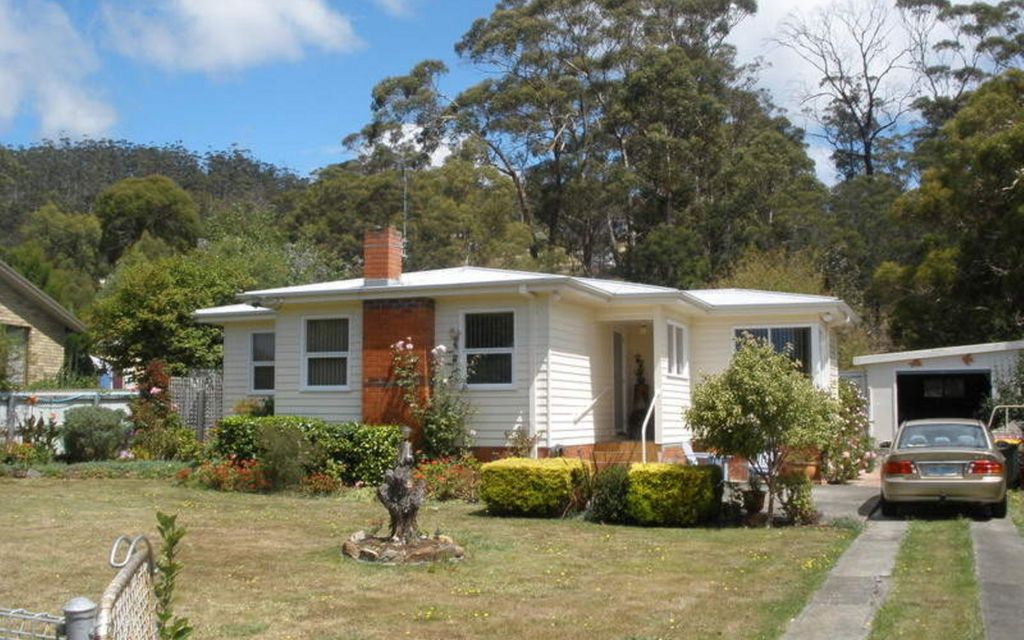 cottage with large landscaped backyard