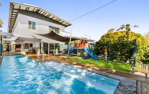 Enjoy the summer in this stunning home by the solar heated lap pool!